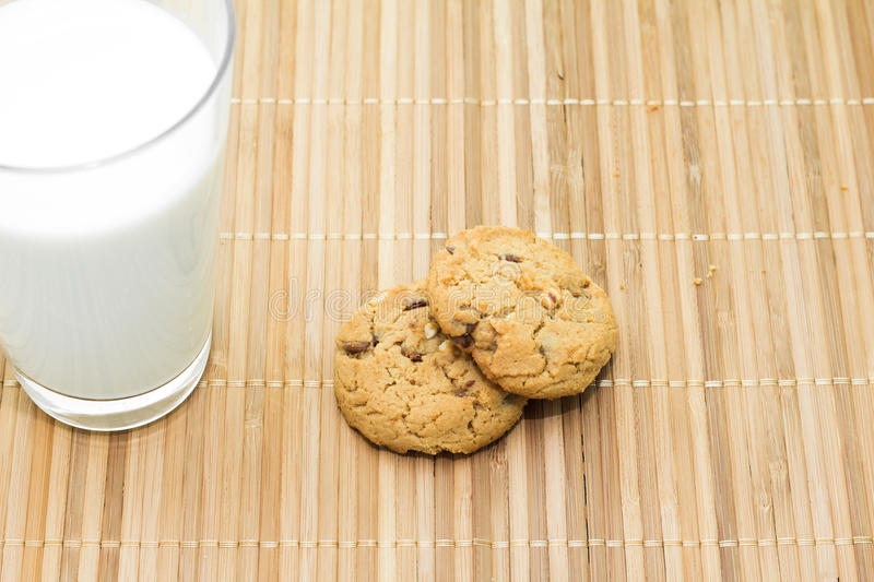 Cookies and a glass of milk on a bamboo table cloth stock photos