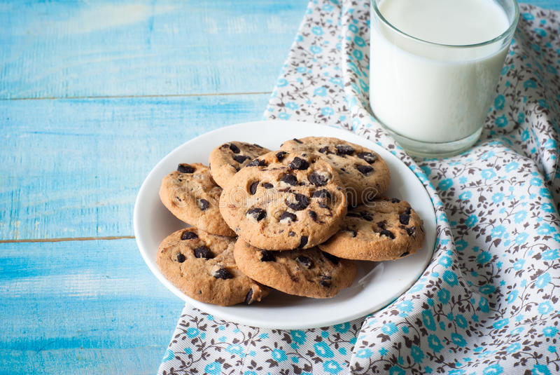 Cookies and a glass of milk. Chocolate chip cookies and a glass of milk on a blue wooden table royalty free stock image