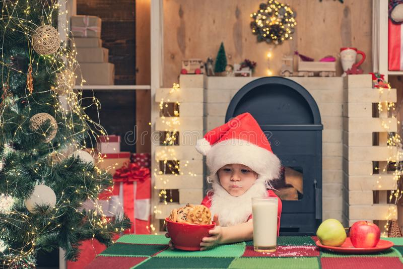 Cookies for kids Santa Claus. Happy Santa Claus - cute boy child eating a cookie and drinking glass of milk at home. Christmas interior stock photography