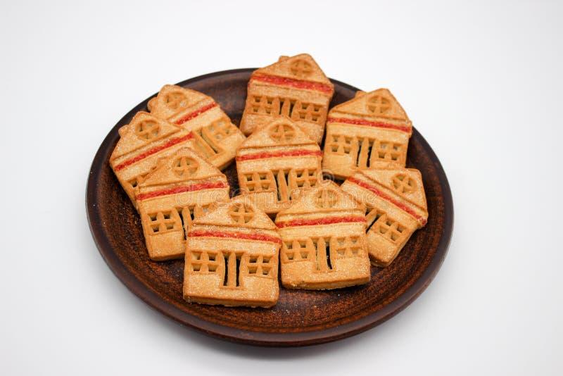 Cookies magn?ficas e deliciosas sob a forma de uma casa de um s? andar com doce de fruta, quais est?o em Clay Plate Imagem isolad foto de stock