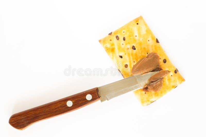 Cookies, manteiga do chocolate e uma faca Fundo branco fotografia de stock royalty free