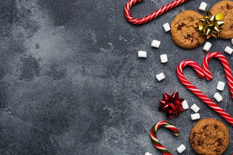 Cookies met chocolade koekjes met kersttanden karamel rood goudlandschap en marshmallow op donkergrijze achtergrond Ruimte-frame  stock foto
