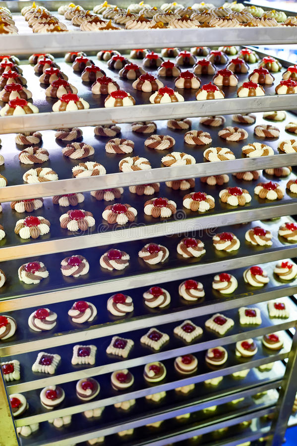 Cookies on metal shelves in confectionery factory. Cookies and cakes on metal shelves in a confectionery factory stock photography