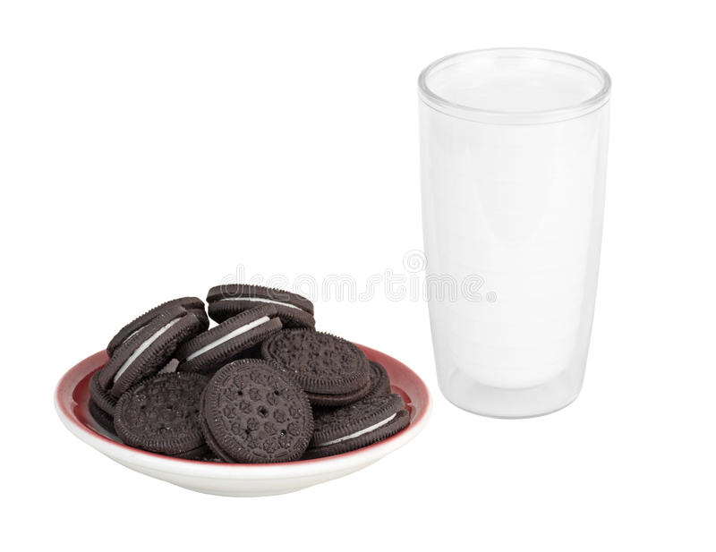 Cookies and Milk. Plate of chocolate cream filled cookies and a glass of milk isolated on white stock images