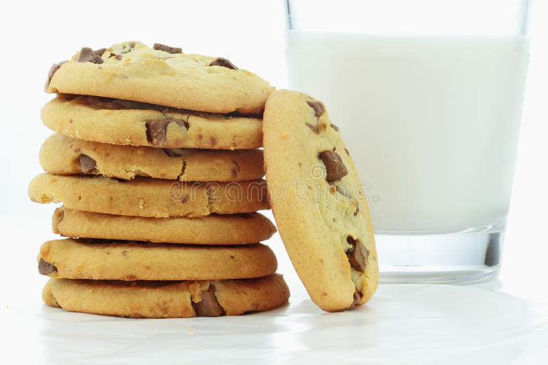 Cookies and Milk. Chocolate chip cookies and a glass of milk on wax paper stock image