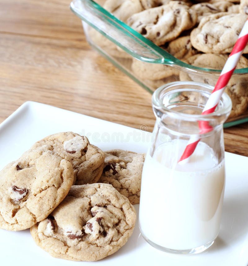 Cookies with milk. Chocolate chip cookies on a plate with a glass of milk royalty free stock photography