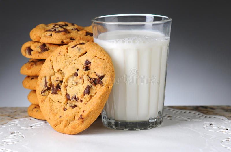 Cookies and Milk. Stack of chocolate chip cookies next to a glass of milk. Horizontal format on a light to dark background stock image