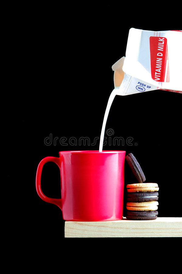 Cookies and Milk. Plastic Cup with a Stack of Cookies and Milk Pouring From Carton on a black background and copyspace royalty free stock image