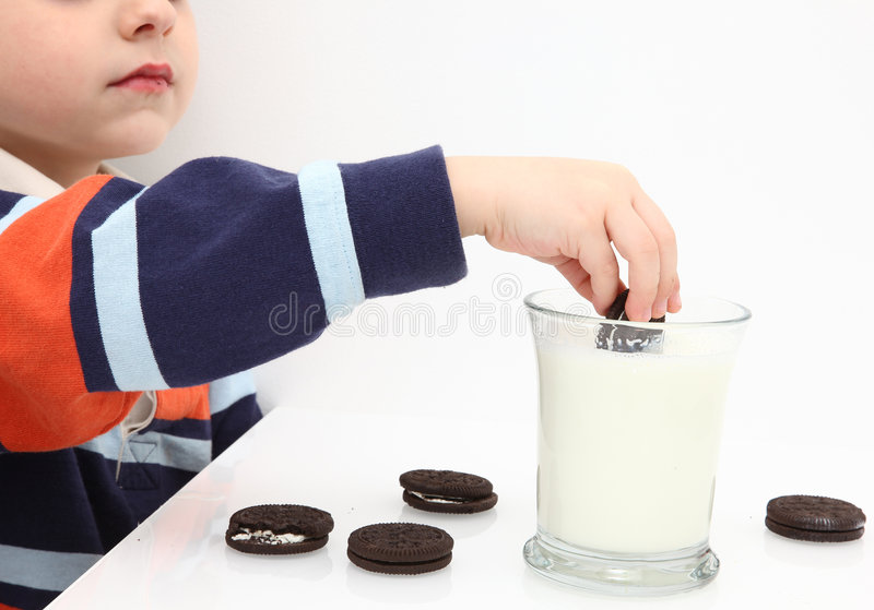 Cookies and Milk. Small boy dunking cookies in milk royalty free stock images
