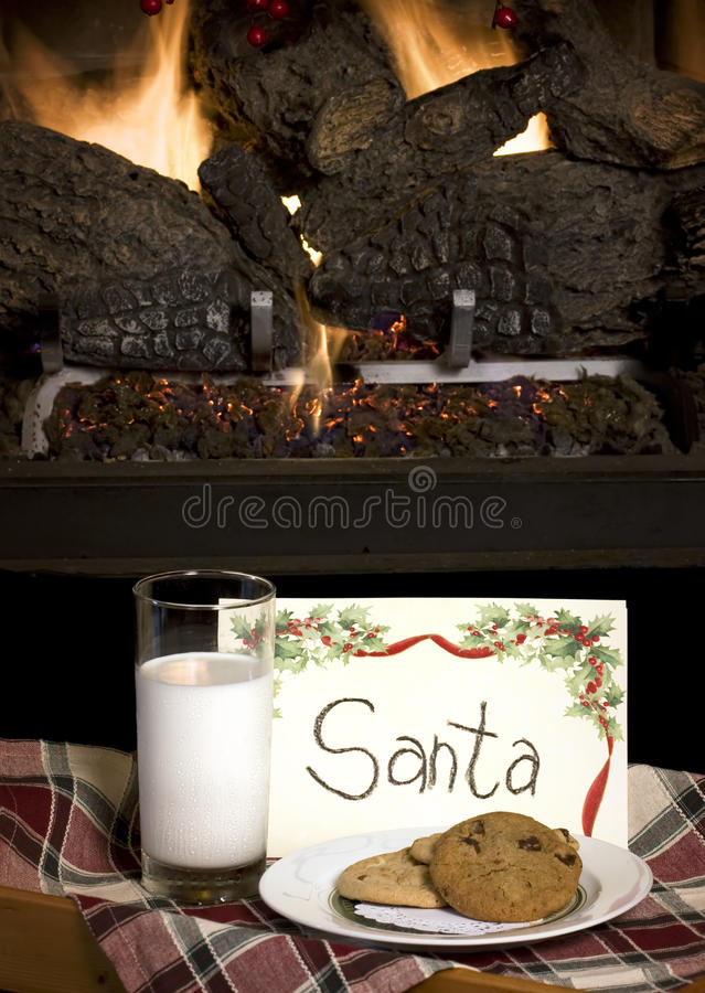 Cookies & Milk for Santa. Cookies and milk left for Santa on tray in front of burning fireplace stock photos