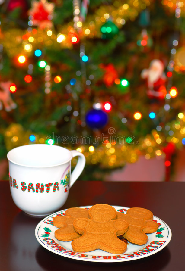 Cookies and Milk for Santa. On a table with a christmas tree in the background royalty free stock images