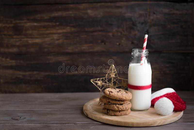 Cookies and Milk for Santa. Traditional Christmas homemade chocolate chip cookies and bottle of milk with Christmas decor on rustic wooden table, copy space royalty free stock photo