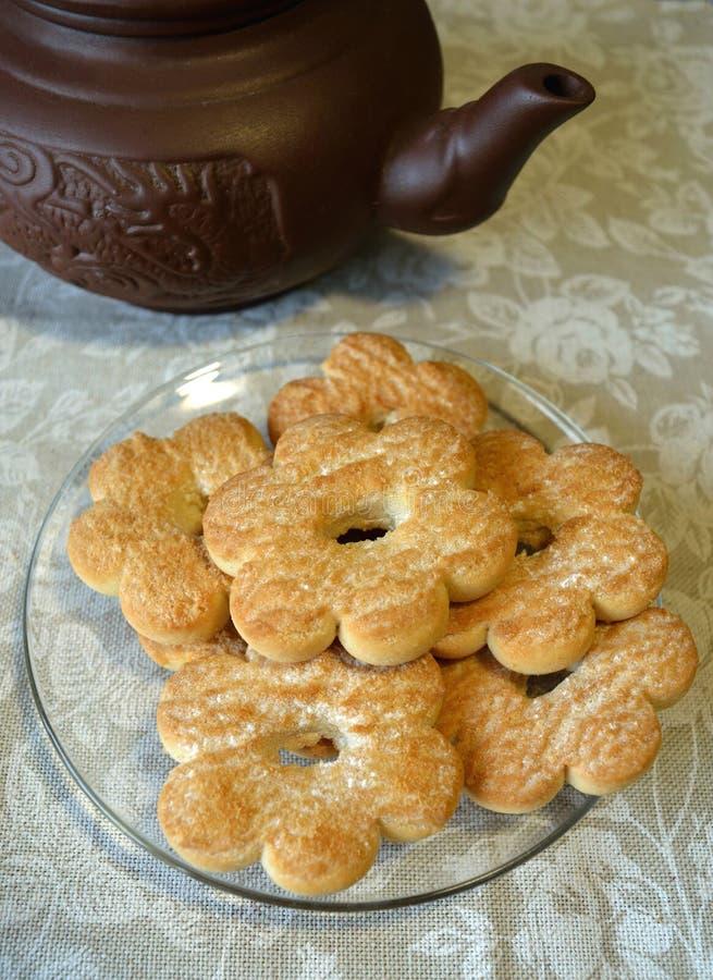 Cookies na forma das flores nos pires transparentes e no bule marrom da argila na toalha de mesa com rosas brancas foto de stock