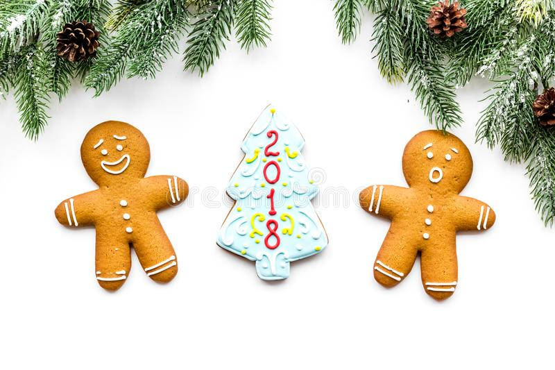 Cookies for New Year. Gingerbread man and spruce with lettering 2018 near spruce branch on white background top view.  royalty free stock photo