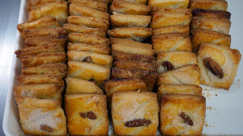 Cookies with nut. Many cookies recently baked, covered with some sugar and with a nut over each one, recently cooked sweet cookies over a tray royalty free stock images