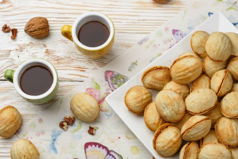 Cookies nuts com leite condensado e turco com café em uma tabela de madeira no estilo do vintage imagens de stock
