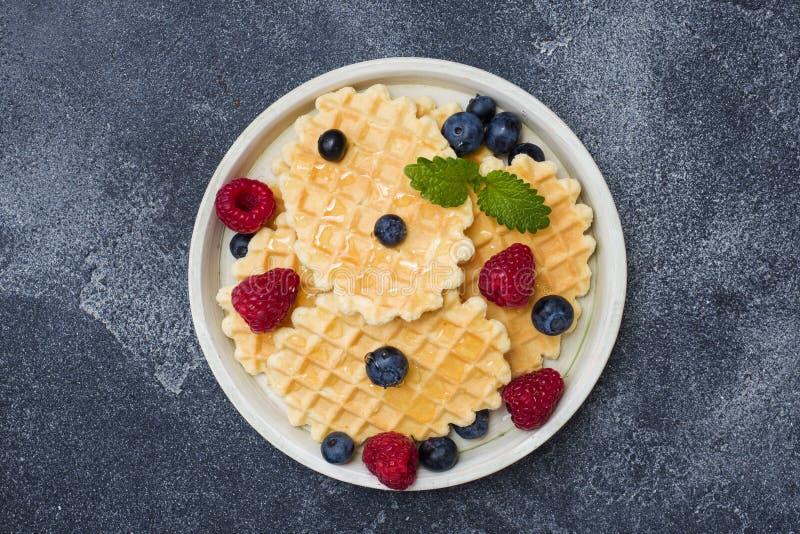 Cookies onduladas do waffle com framboesas e os mirtilos frescos em um fundo concreto escuro Copie o espa?o fotografia de stock