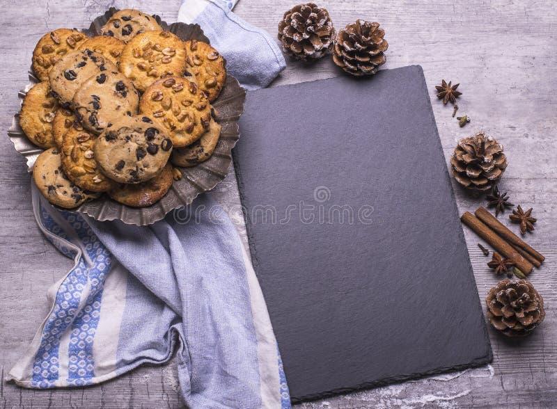 Cookies recentemente cozidas deliciosas do Natal com placa preta para a receita em uma tabela de madeira cinzenta foto de stock