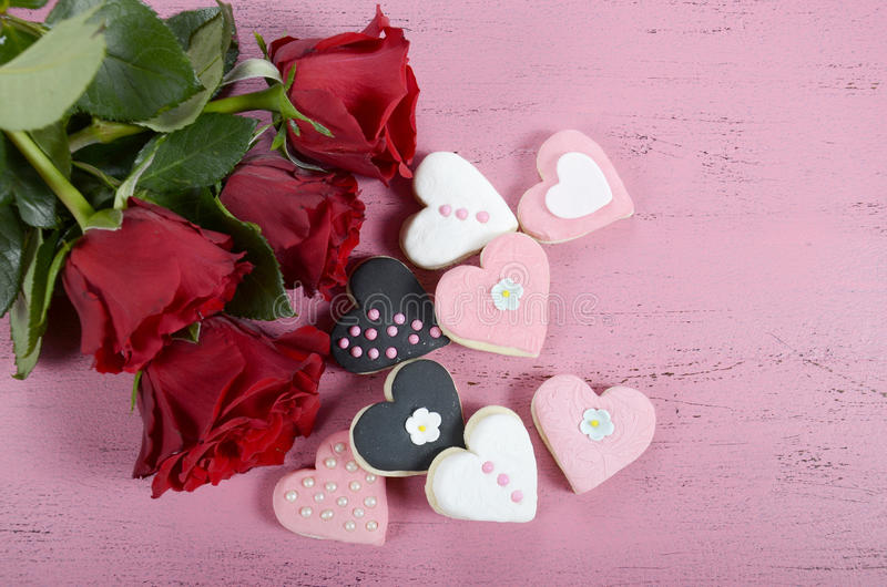 Cookies românticas do rosa da forma do coração, as brancas e as pretas com rosas vermelhas imagem de stock