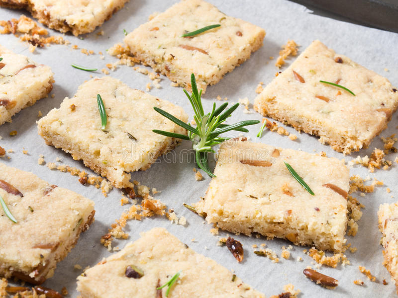 Cookies with rosemary and pignoli nuts. Butter cookies with rosemary, pignoli and pistachio nuts on baking parchment, decorated with rosemary sprigs stock images