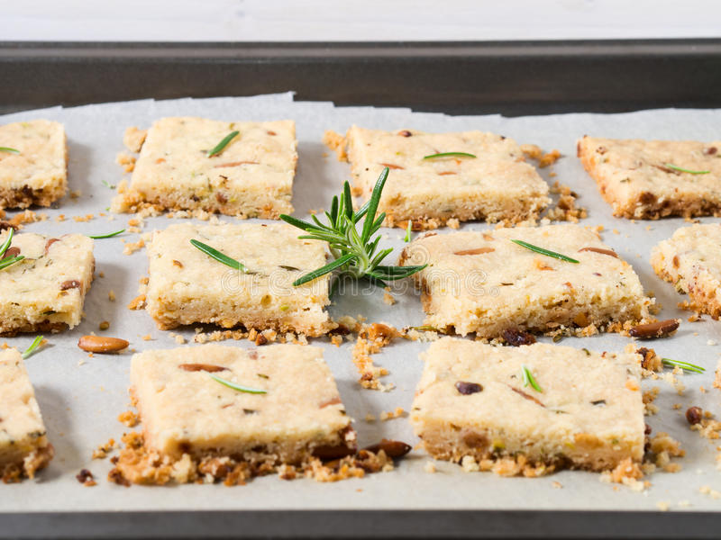 Cookies with rosemary and pignoli nuts. Butter cookies with rosemary, pignoli and pistachio nuts on baking parchment, decorated with rosemary sprigs stock photo