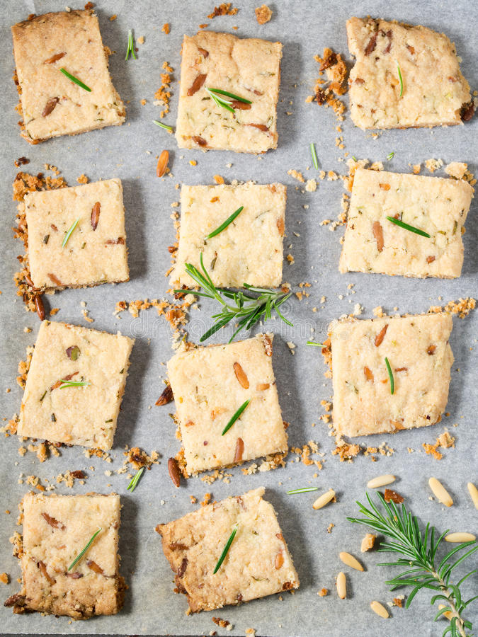 Cookies with rosemary and pignoli nuts. Butter cookies with rosemary, pignoli and pistachio nuts on baking parchment, decorated with rosemary sprigs stock image