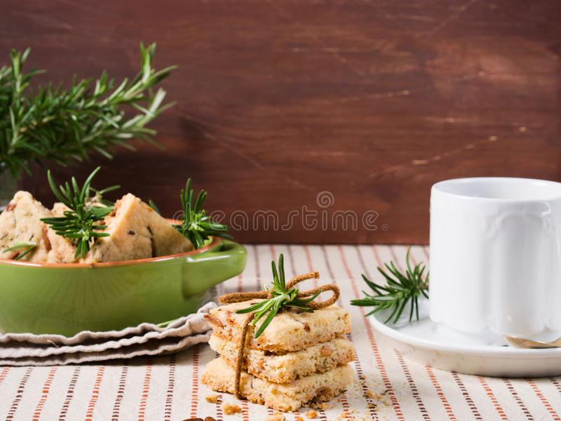 Cookies with rosemary and pignoli nuts. Butter cookies with rosemary, pignoli and pistachio nuts on table cloth with rosemary sprigs and a hot beverage in the royalty free stock photography