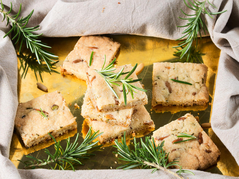 Cookies with rosemary and pignoli nuts on golden tray. Butter cookies with rosemary, pignoli and pistachio nuts on golden tray, decorated with rosemary sprigs royalty free stock image