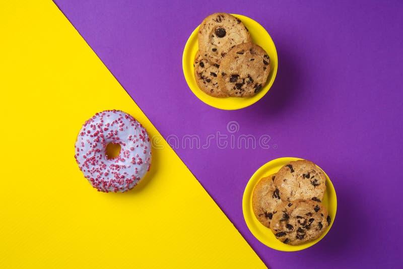 Cookies saborosos com pedaços de chocolate e a filhós vitrificada no fundo da cor fotografia de stock
