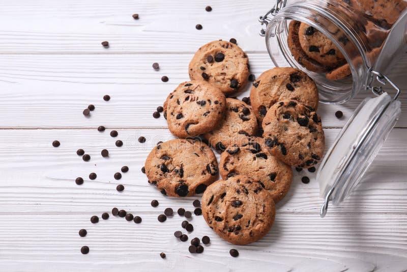 Cookies saborosos com pedaços de chocolate e o frasco virado na tabela de madeira branca fotografia de stock royalty free