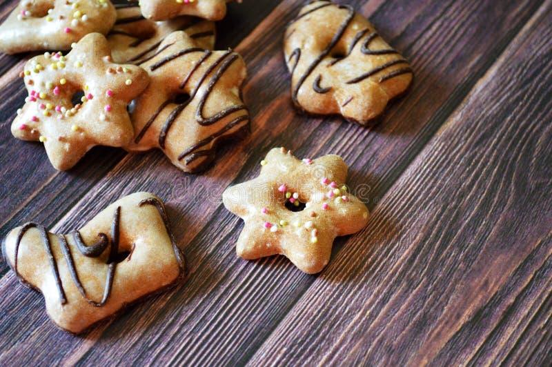 Cookies saborosos do gengibre com esmalte do açúcar em um fundo de madeira foto de stock