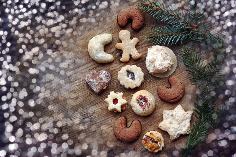 Cookies, Santa Claus, fir twigs and glitter spots on a wooden background royalty free stock photos