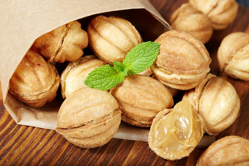 Cookies in a shape of nuts with condensed milk cream filling royalty free stock photos