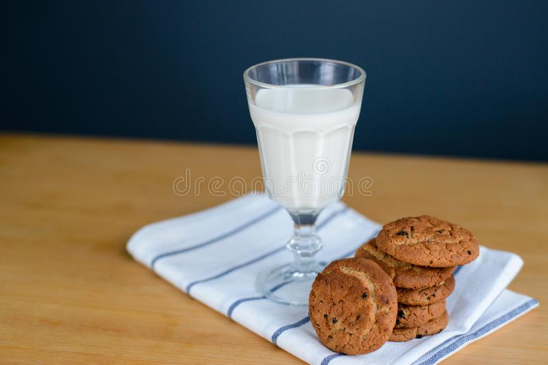 Cookies stack with raisins and milk on rag on table stock images