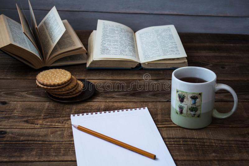 Cookies and tea open book pencil notebook. On wooden background royalty free stock image
