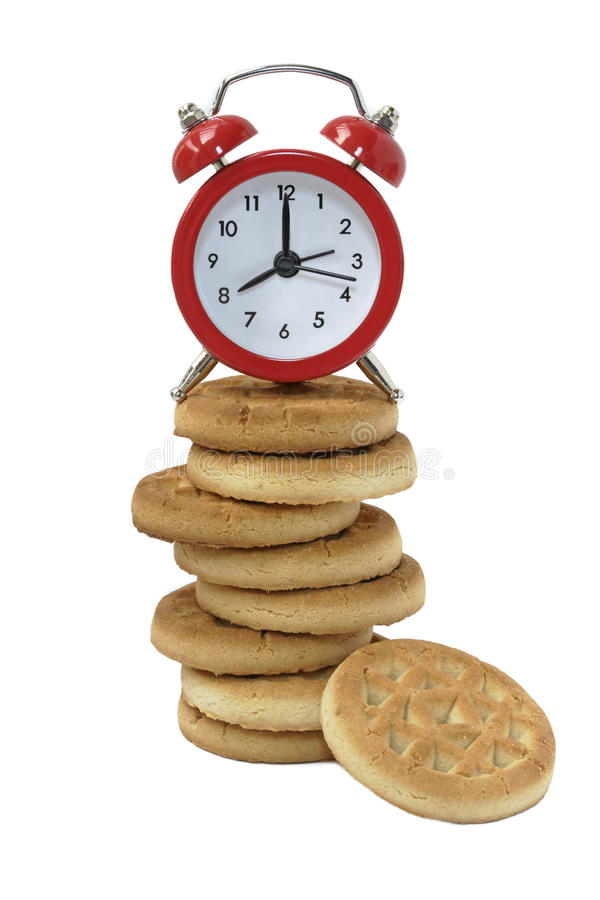 Cookies tower and alarm clock. On a white background insulated stock image