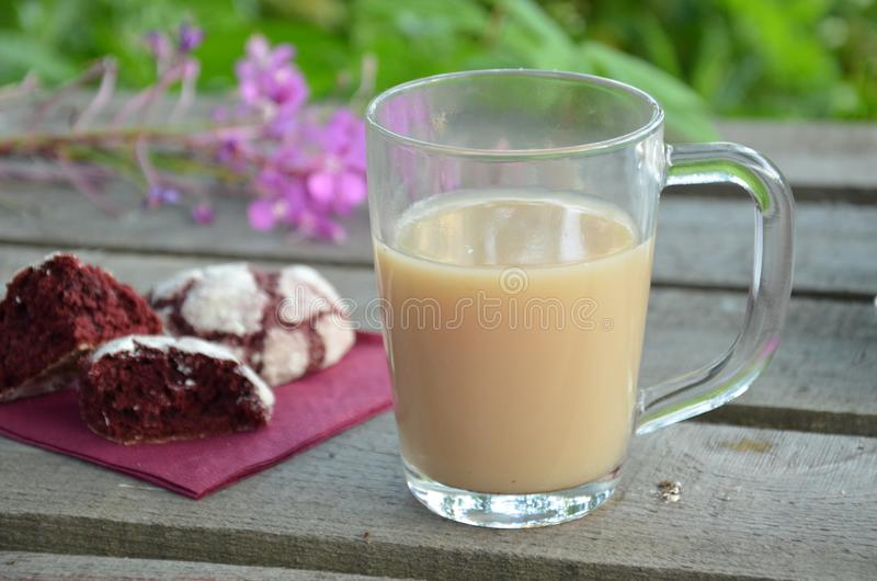 Cookies vermelhas de veludo ao lado de uma xícara de café manhã ensolarada da mola ou do verão Flor roxa cor-de-rosa foto de stock