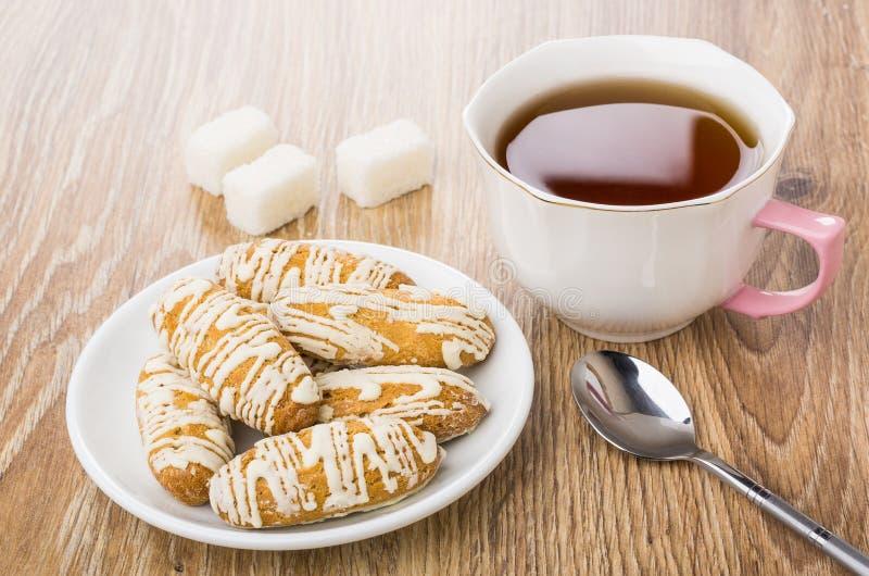 Cookies vitrificadas em uns pires, açúcar, colher de chá, copo do chá imagem de stock royalty free
