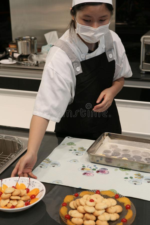 Beijing China - June 10, 2018: A female chef treats visitors with ready-made cookies, beautifully served on plates. royalty free stock image