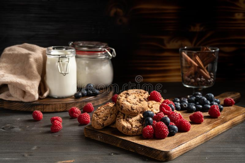 Cookies on wooden board next to berries and cinnamon sticks stock photo