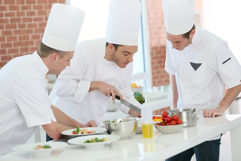 Cookin utbildning med studenter i restaurang royaltyfri bild