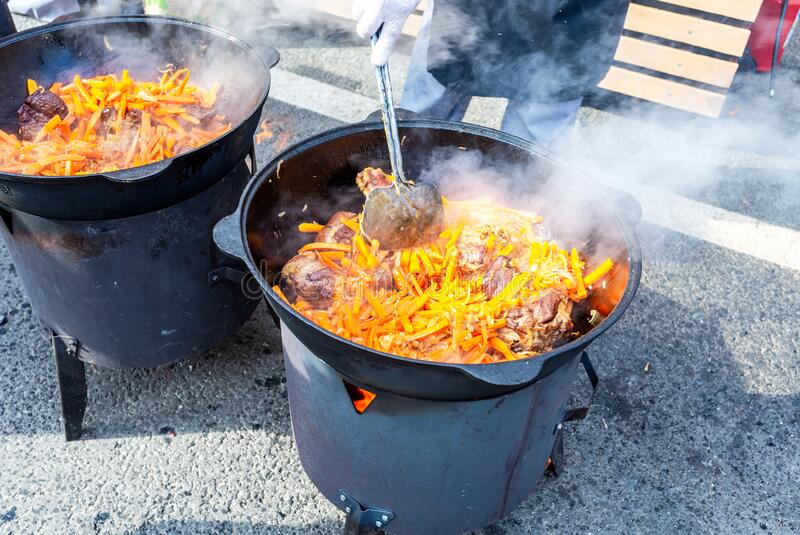 Cooking appetizing traditional food in a large cauldrons royalty free stock images