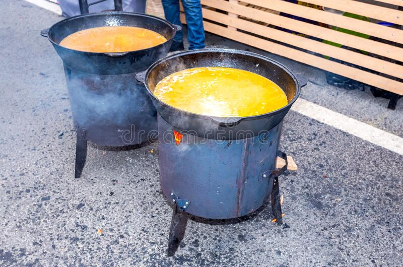 Cooking appetizing traditional food in a large cauldrons royalty free stock photo
