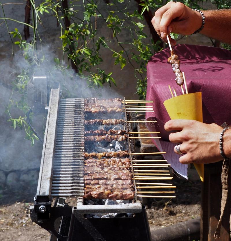 Cooking arrosticini, an Italian specialty of meat skewers, on their special grill.  royalty free stock photos