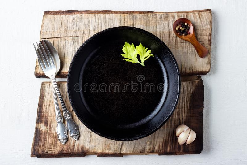 Cooking background concept. Empty rustic black cast iron plate, spice and cutlery over wooden background royalty free stock photography