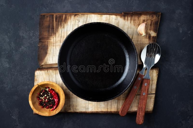 Cooking background concept. Vintage black iron pan on a rustic burnt cutting board and cutlery. Top view stock photo