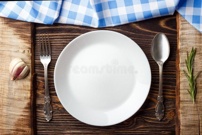 Cooking background concept. Vintage cutting board, blue checkered napkin, plate and cutlery. Top view stock photos