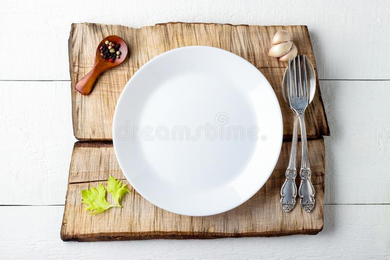 Cooking background concept. Empty white plate, spice and cutlery. Over wooden background royalty free stock photo