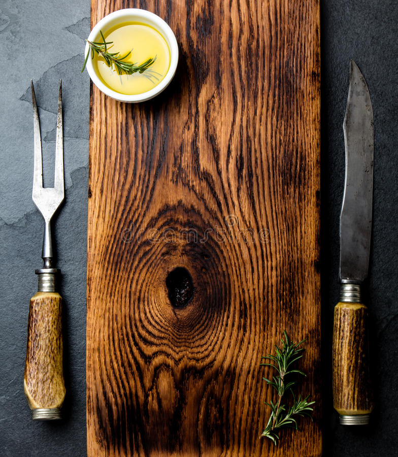 Cooking background concept. Vintage cutting board with cutlery. Top view royalty free stock photos