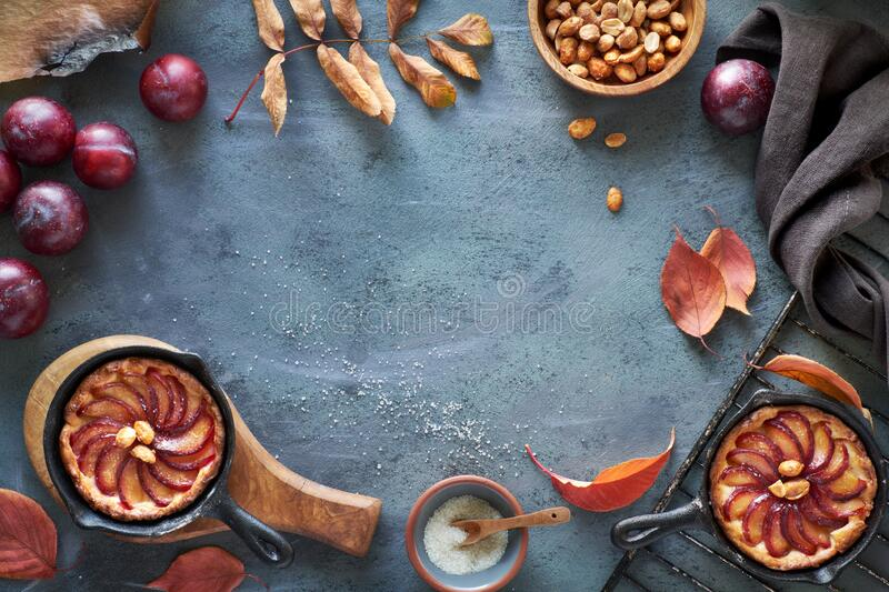 Cooking background with red plums, plum crumble cakes, towel, caramelized peanuts, autumn leaves, copy-space. Cooking background with red plums, plum crumble stock photo